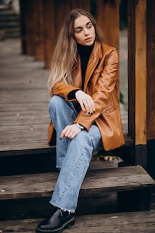 Young woman in jacket sitting on stairs