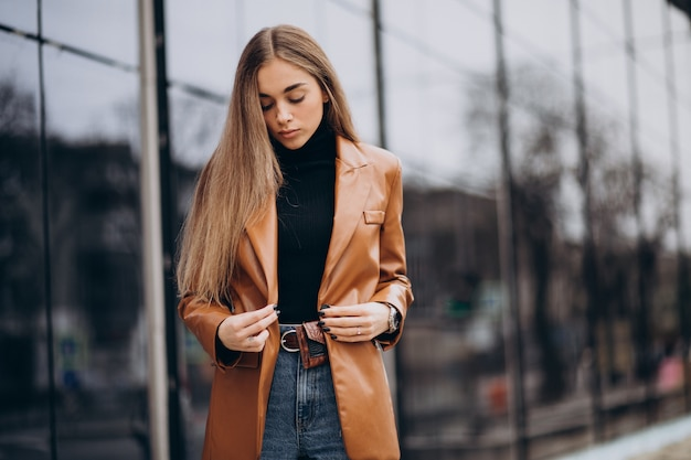 Young woman in jacket walking out in the city