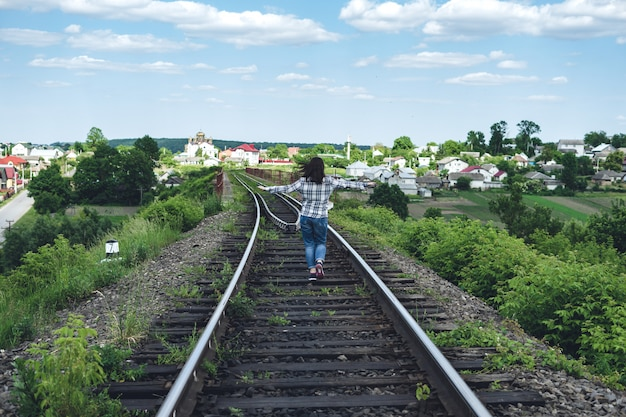 Young woman in jeans and shirt runs along the railway track