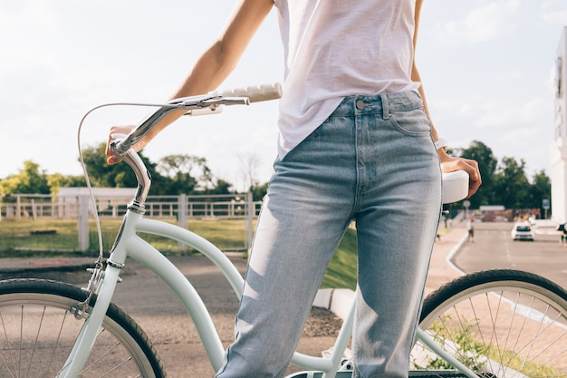 Young woman in jeans and t-shirt with a bicycle in the park in summer