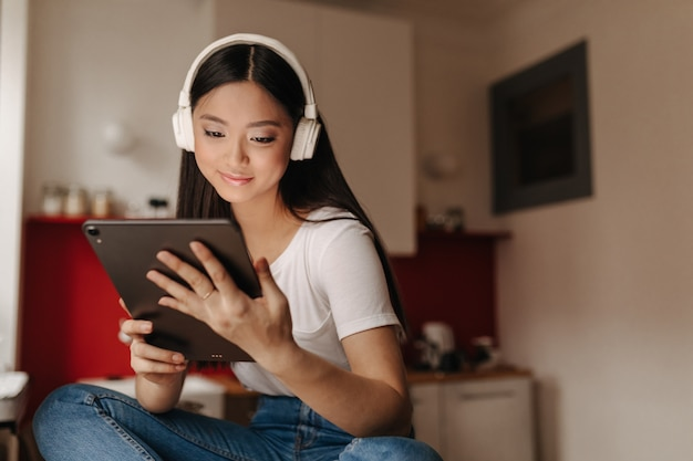Young woman in jeans and white t-shirt looks into tablet and listens to music in headphones