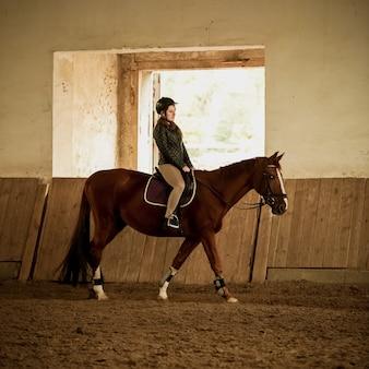 Young woman jockey doing training at indoor arena