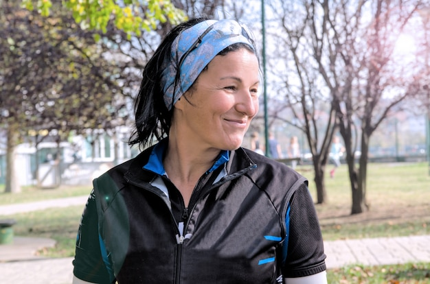 Young woman jogger portrait in the park.sports middle aged woman smiling