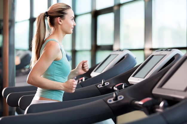 Young woman jogging at gym on treadmill