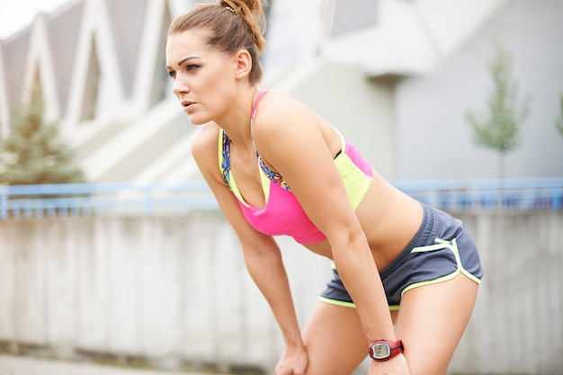 Giovane donna che pareggia o che corre all'aperto. questo tipo di sport può essere davvero stancante