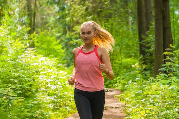 Young woman jogging through a sunny forest