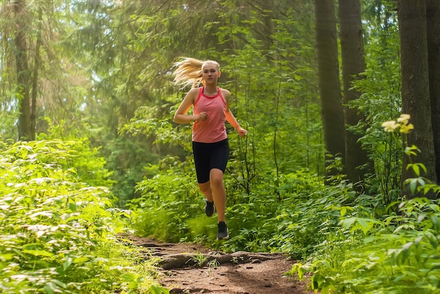 Young woman jogging on a trail in a mountain forest