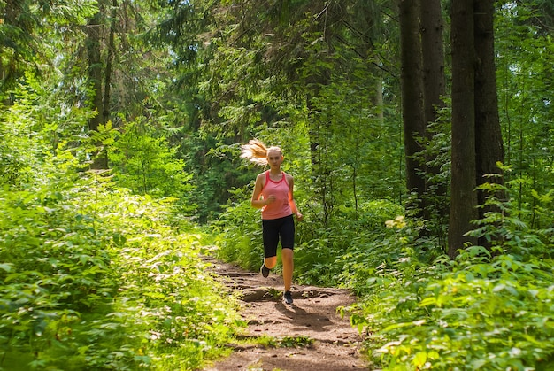 Young woman jogging on a trail in a sunny mountain forest
