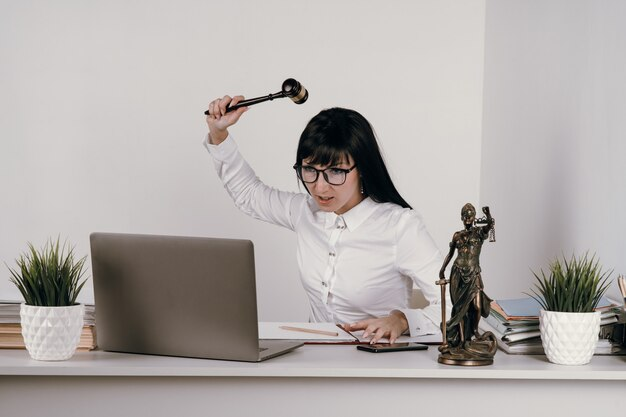 Молодая женщина-судья выносит приговор в офисе или дистанционно.