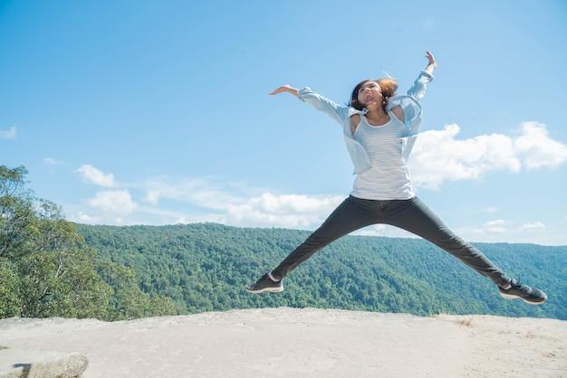 太陽の光のためにマウンテンビューでジャンプする若い女性 Premium写真