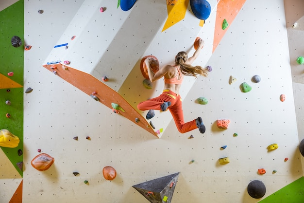 Young woman jumping on handhold in indoor bouldering gym