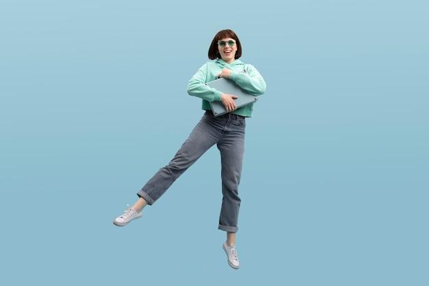 青に孤立してジャンプ若い女性
