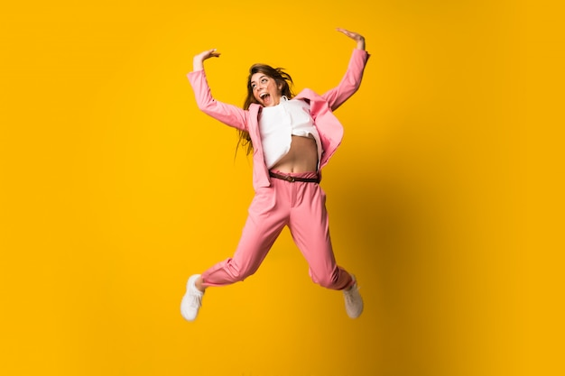 Young woman jumping over isolated yellow wall making victory gesture
