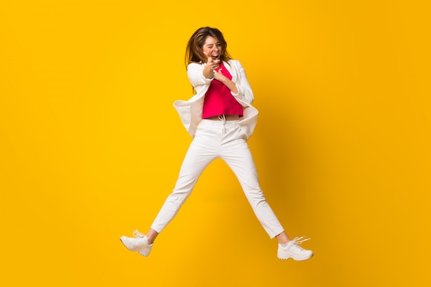Young woman jumping over isolated yellow wall pointing to the front