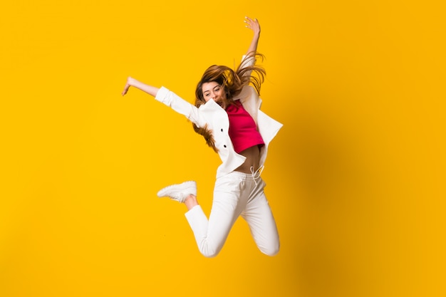 Young woman jumping over isolated yellow wall