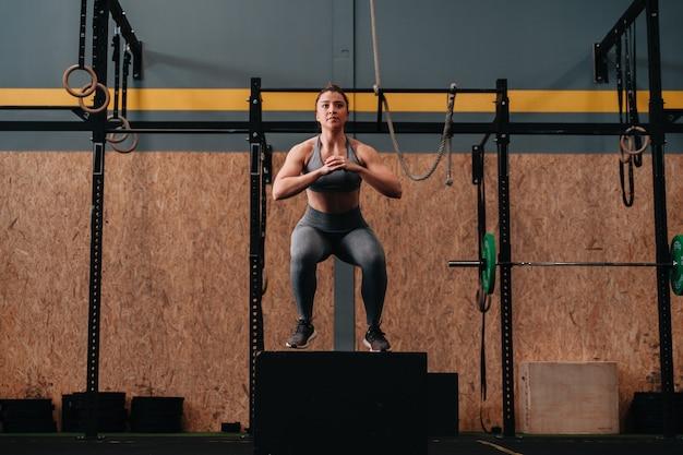 Молодая женщина прыгает на коробке, делая упражнения crossfit