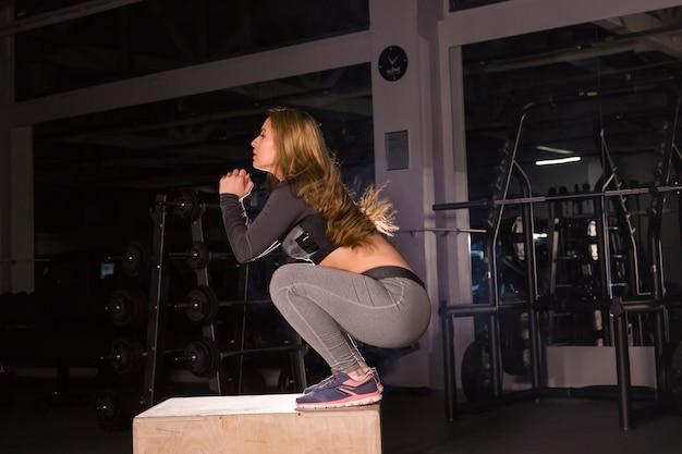 クロスフィットジムでボックスにジャンプする若い女性。