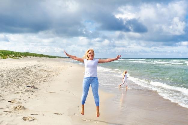 リトアニアのバルト海のビーチでジャンプする若い女性小さな女の子がビーチに沿って散歩します。