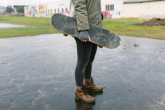 Молодая женщина прыгает через скейтборд