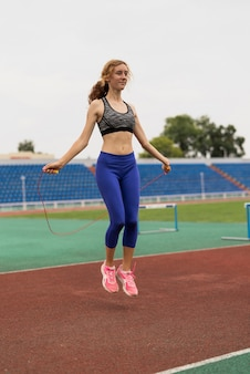 Молодая женщина, прыжки через скакалку на стадионе