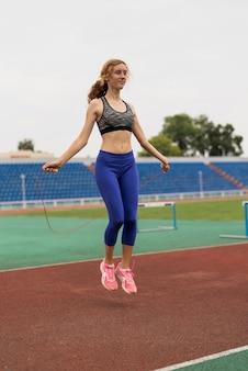 Young woman jumping rope at stadium