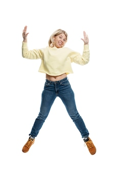 Young woman jumping. smiling blonde in a yellow sweater and jeans. movement and energy.