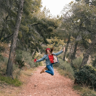 Young woman jumping over the trail in the mountain