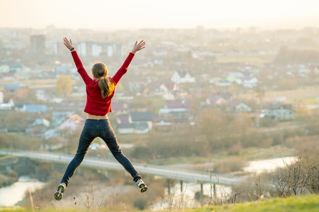 Young woman jumping with outstretched arms and legs outdoors on a distant city