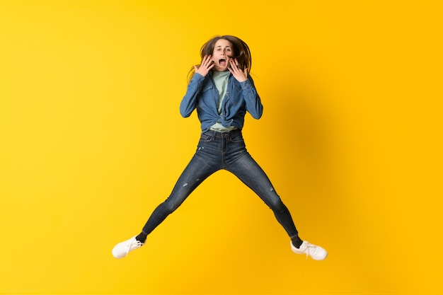 Young woman jumping over yellow background