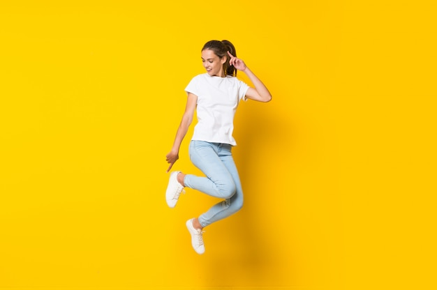 Young woman jumping  on yellow wall