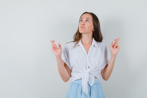 손가락을 유지하는 젊은 여자가 흰 블라우스와 밝은 파란색 치마를 입고 잠겨있는 찾고