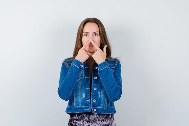 Молодая женщина держит пальцы на носу в джинсовой куртке, платье и выглядит смешно, вид спереди.