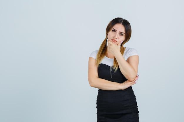 Giovane donna che tiene la mano sul mento e sembra pensierosa