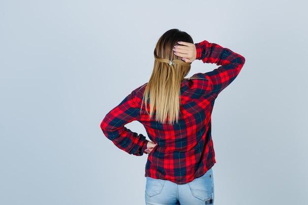 Giovane donna che tiene la mano dietro la testa in camicia a quadri, jeans e guardando pensieroso, vista posteriore.