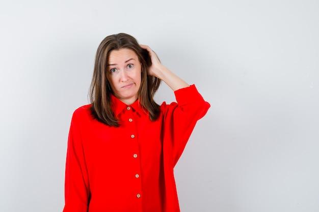 Giovane donna che tiene la mano sulla testa in camicetta rossa e sembra esitante, vista frontale.