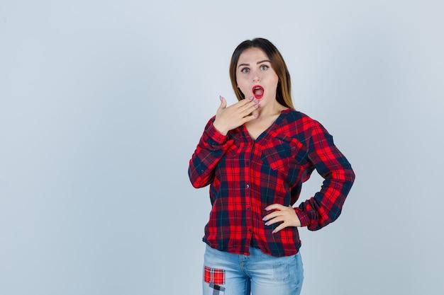 チェックシャツのあごに手を置いてショックを受けた若い女性、正面図。