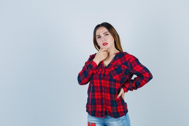 チェックシャツのあごに手を置いて、思慮深く、正面図を探している若い女性。