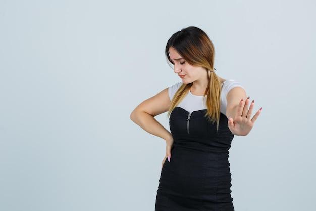 停止ジェスチャーを示している間腰に手を保つ若い女性
