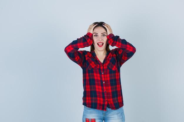 Giovane donna che tiene le mani sulla testa in camicia a quadri e sembra felice, vista frontale.