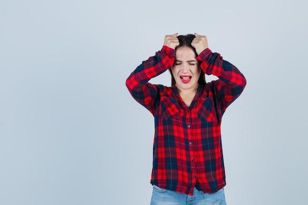 Giovane donna che tiene le mani sulla testa in camicia a quadri e sembra irritata, vista frontale.