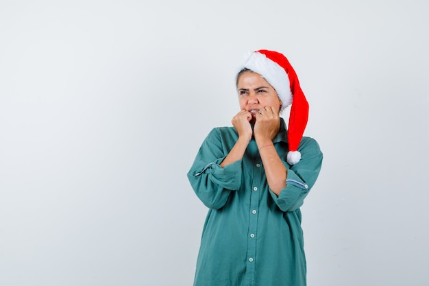 Giovane donna che tiene le mani vicino alla bocca in camicia, cappello da babbo natale e sembra terrorizzata. vista frontale.