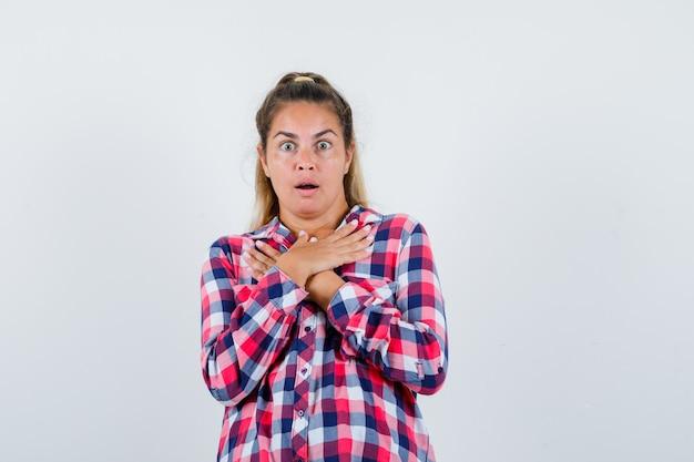 Молодая женщина держит руки на груди в повседневной рубашке и выглядит потрясенной, вид спереди.