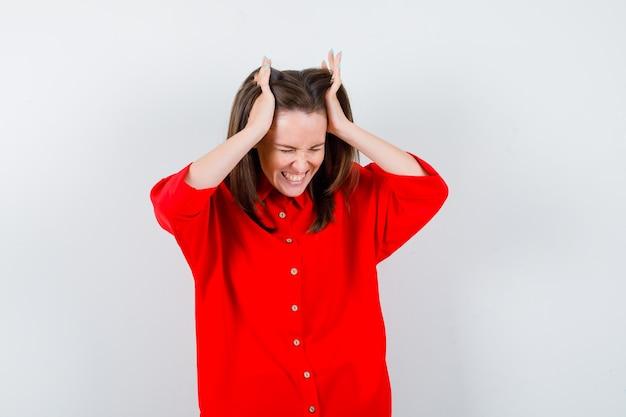 赤いブラウスで頭を抱えてイライラしている若い女性、正面図。