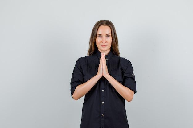 Giovane donna che tiene le mani nel gesto di preghiera in camicia nera e sembra speranzoso