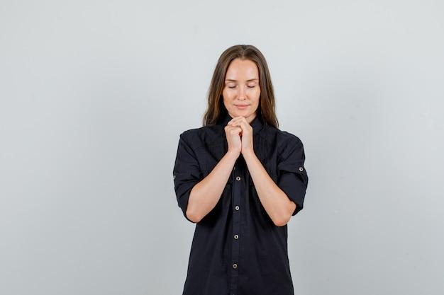 Giovane donna che tiene le mani nel gesto di preghiera in camicia nera