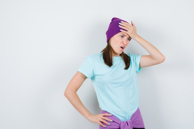 Young woman keeping one hand on forehead, another hand on hip in blue t-shirt, purple beanie and looking shocked. front view.