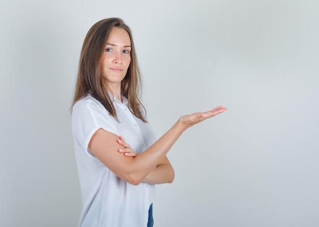 Молодая женщина держит открытую ладонь в белой футболке, джинсах и выглядит веселой
