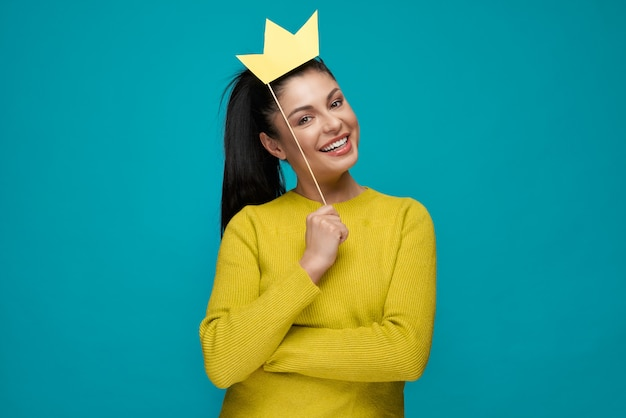 Young woman keeping paper crown and posing on blue isolated background.