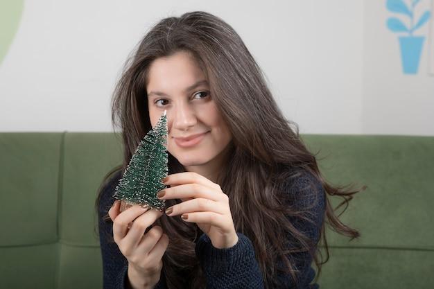 Giovane donna che tiene un piccolo albero di pino nelle sue mani.