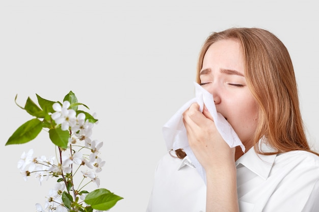 Young woman keeps handkerchief near nose, has allergy to tree blossom, wears elegant shirt, isolated on white. people, sensitivity, allergy, sickness, sneezing concept.
